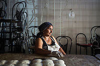 "ROME, ITALY - 3 JULY 2016: Gipsy Queen member Micescu Mieila (49) relaxes after shaping dough for pitas, before heading to a food stand at the iFest, an alternative music festival, here in the Astra 19 social center in Rome, Italy, on July 3rd 2016.<br /> <br /> The Gipsy Queens are a travelling catering business founded by Roma women in Rome.<br /> <br /> In 2015 Arci Solidarietà, an independent association for the promotion of social development, launched the ""Tavolo delle donne rom"" (Round table of Roma women) to both incentivise the process of integration of Roma in the city of Rome and to strengthen the Roma women's self-esteem in the context of a culture tied to patriarchal models. The ""Gipsy Queens"" project was founded by ten Roma women in July 2015 after an event organised together with Arci Solidarietà in the Candoni Roma camp in the Magliana, a neighbourhood in the South-West periphery of Rome, during which people were invited to dance and eat Roma cuisine. The goal of the Gipsy Queen travelling catering business is to support equal opportunities and female entrepreneurship among Roma women, who are often relegated to the roles of wives and mothers."