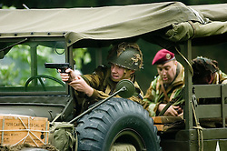 A reenactor portraying a British Paratrooper fires a 1911 Colt .45 from the cab of a dodge weapons carrier during a Battle reenactment at Sheffield Fayre <br />