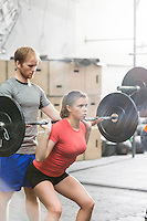 Man assisting woman in lifting barbell in crossfit gym