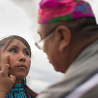 Kayla Kaamasee paints red cay on the face of Edward Lewis, both members of the Red Clay dance group before the start of the parade in Zuni Thursday.