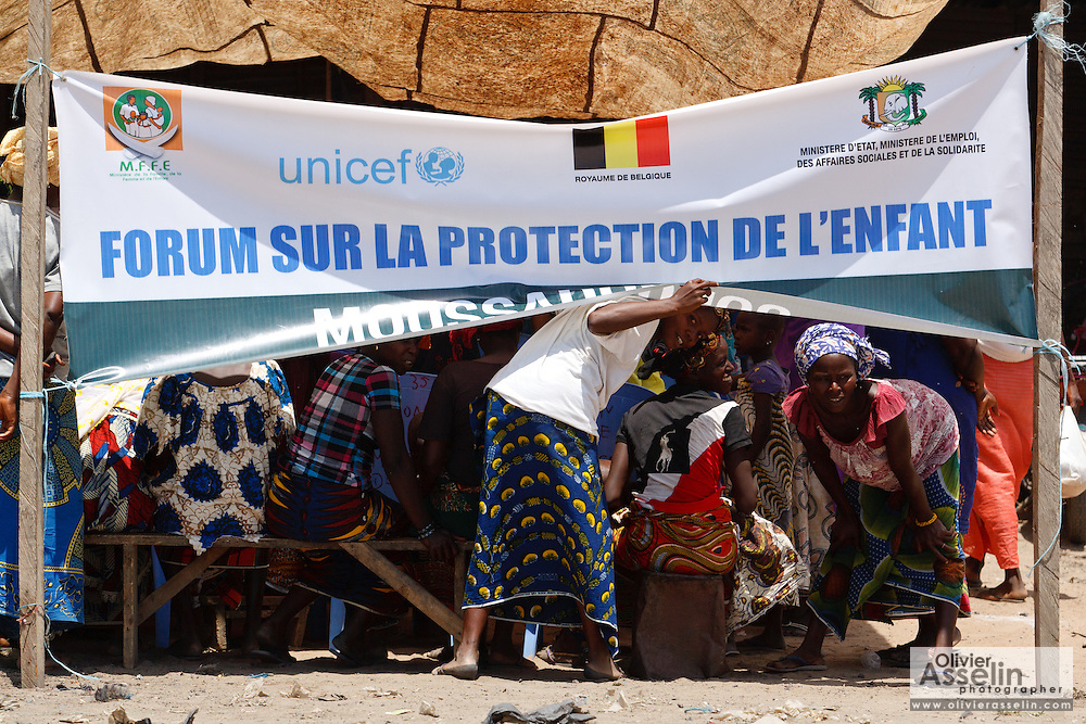 Women look from under a banner as they attend a UNICEF-sponsored forum on child protection in the town of Moussadougou, Bas-Sassandra region, Cote d'Ivoire on Monday March 5, 2012.