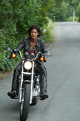 African American woman riding a motorcycle on a country road