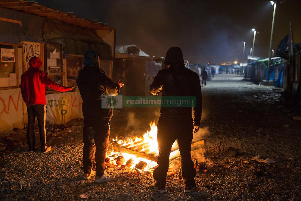 """Dschungel von Calais: Das wilde Fl¸chtlingslager wird ger‰umt und die Fl¸chtlinge in Aufnahmezentren verteilt / 241016 ***Calais, Pas-de-Calais, France - 24.10.2016    <br />  <br /> Refugees warm on a fire. Start of the eviction on the so called îJungle"""" refugee camp on the outskirts of the French city of Calais. Refugees and migrants leaving the camp to get with buses to asylum facilities in the entire country. Many thousands of migrants and refugees are waiting in some cases for years in the port city in the hope of being able to cross the English Channel to Britain. French authorities announced a week ago that they will evict the camp where currently up to up to 10,000 people live.<br /> <br /> <br /> Fluechtlinge waermen sich an einem Feuer. Beginn der Raeumung des so genannte îJungleî-Fluechtlingscamp in der franzˆsischen Hafenstadt Calais. Fluechtlinge und Migranten verlassen das Camp um mit Bussen zu unterschiedlichen Asyleinrichtungen gebracht zu werden. Viele tausend Migranten und Fluechtlinge harren teilweise seit Jahren in der Hafenstadt aus in der Hoffnung den Aermelkanal nach Groflbritannien ueberqueren zu koennen. Die franzoesischen Behoerden kuendigten vor einigen Wochen an, dass sie das Camp, indem derzeit bis zu bis zu 10.000 Menschen leben raeumen werden. <br /> <br /> Photo: Bjoern Kietzmann"""