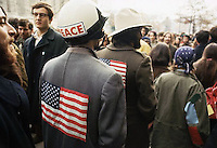 1972, USA --- Men wear American flags sewn to the back of their coats at a rally opposing the Vietnam War. --- Image by © Owen Franken/CORBIS