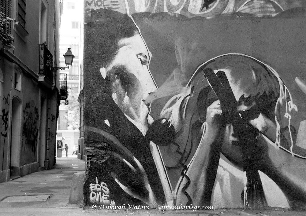 Barrio Gotica, Barcelona, Spain 2004; Contrast of old architecture and urban art graffiti mural of 2 men suggestive of guns and gang culture