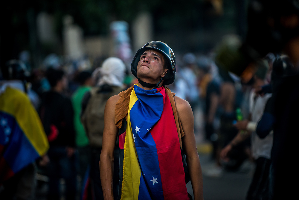 CARACAS, VENEZUELA - MAY 20, 2017:  An anti-government protester during clashes with government security forces. The streets of Caracas and other cities across Venezuela have been filled with tens of thousands of demonstrators for nearly 100 days of massive protests, held since April 1st. Protesters are enraged at the government for becoming an increasingly repressive, authoritarian regime that has delayed elections, used armed government loyalist to threaten dissidents, called for the Constitution to be re-written to favor them, jailed and tortured protesters and members of the political opposition, and whose corruption and failed economic policy has caused the current economic crisis that has led to widespread food and medicine shortages across the country.  Independent local media report nearly 100 people have been killed during protests and protest-related riots and looting.  The government currently only officially reports 75 deaths.  Over 2,000 people have been injured, and over 3,000 protesters have been detained by authorities.  PHOTO: Meridith Kohut