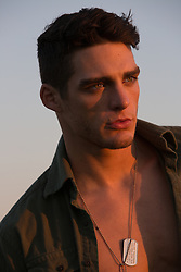 All American good looking man with green eyes and black hair outdoors at sunset