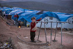 A refugee child from the country side of Aleppo plays with one of the water supplies at Qah's refugee camp Idlib province, Syria. Situated 7 km away from the Turkish border Qah refugee camp is one of the three refugee camps in the area -inside Syria's territory- with an estimated number of 3,200 refugees and growing by the day. Build in August 2012 by the help of Libyan al-Yosser charity and with the provision of tents, blankets etc of the Syrian National Council., Syria, February 6, 2013. Photo by Daniel Leal-Olivas / i-Images.