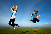 Two young girls leaping into the air in a field.