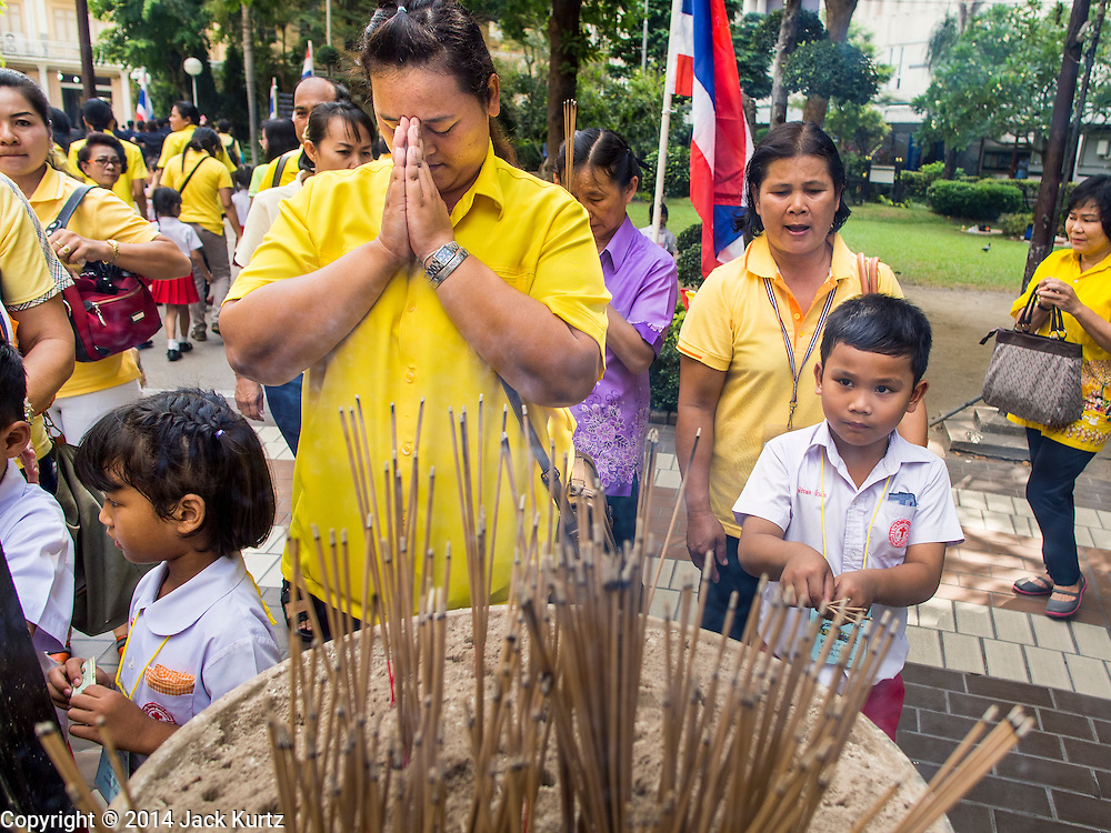 28 NOVEMBER 2014 - BANGKOK, THAILAND: People on the plaza in front of Siriraj Hospital pray for Bhumibol Adulyadej, the King of Thailand. The King was born on December 5, 1927, in Cambridge, Massachusetts. The family was in the United States because his father, Prince Mahidol, was studying Public Health at Harvard University. He has reigned since 1946 and is the world's currently reigning longest serving monarch and the longest serving monarch in Thai history. Bhumibol, who is in poor health, is revered by the Thai people. His birthday is a national holiday and is also celebrated as Father's Day. He is currently hospitalized in Siriraj Hospital, recovering from a series of health setbacks. Thousands of people come to the hospital every day to sign get well cards for the King. People wear yellow at events associated with the King because he was born on a Monday, and yellow is Monday's color in Thai culture. It's also the color of the monarchy.       PHOTO BY JACK KURTZ