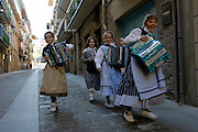 Girls dressed up as traditional basque women and playing the accordion in the streets of Getaria.