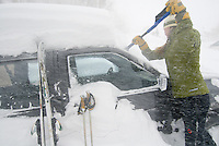 A young woman clears snow from her car during a snowstorm in Jackson Hole, Wyoming.