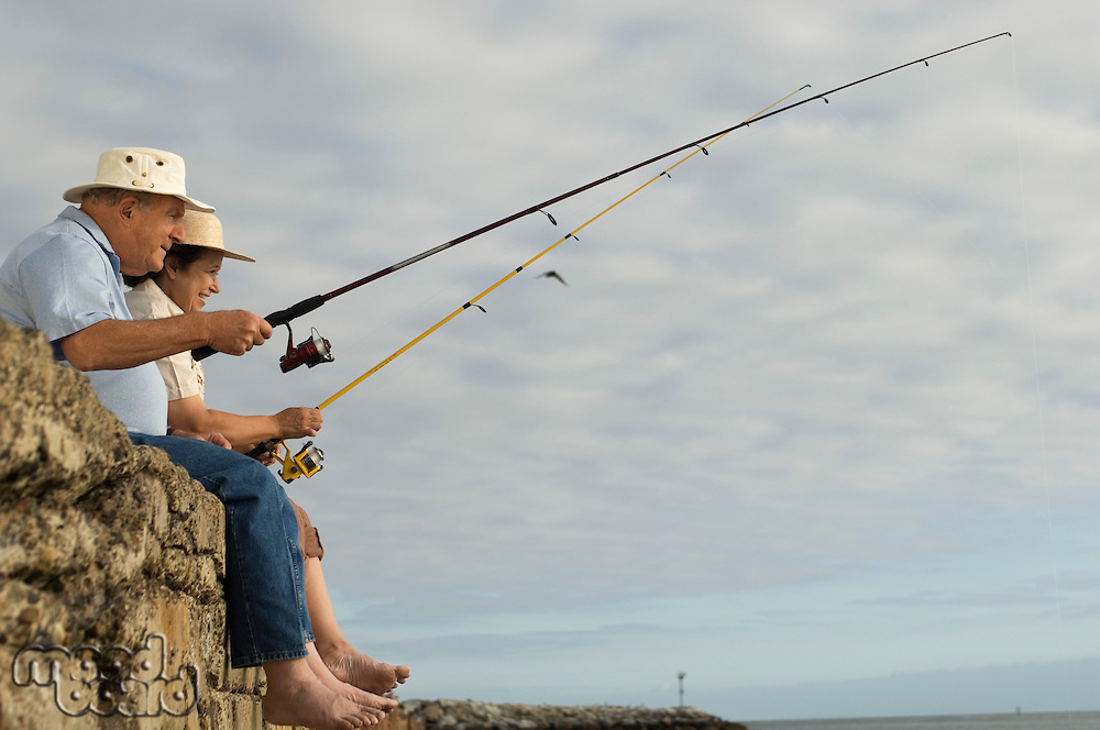 Senior couple fishing at ocean