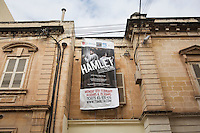 SLIEMA, MALTA - 8 FEBRUARY 2016: A banner advertises the touring Hamlet, performed by the Shakespeare's Globe theatre company,  at the Salesian Theatre in Sliema, Malta, on February 8th 2016.<br /> <br /> The touring Hamlet, performed by the Shakespeare's Globe theatre company, is part of the Globe to Globe tour that set off in April 2014 (on the 450th anniversary of Shakespeare's birth) with the ambitious intention of visiting every country in the world over 2 years. The crew is composed of a total of sixteen men and women: four stage managers and twelve twelve actors  actors perform over two dozen parts on a stripped-down wooden stage. So far Hamlet has been performed in over 150 countries, to more than 100,000 people and travelled over 150,000 miles. The tour was granted UNESCO patronage for its engagement with local communities and its promotion of cultural education. Hamlet was also played for many dsiplaced people around the world. It was performed in the Zaatari camp on the border between Syria and Jordan, for Central African Republic refugees in Cameroon, and for Yemeni people in Djibouti. On February 3rd it was performed to about 300 refugees in Calais at the camp known as the Jungle.