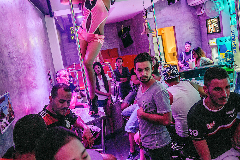 Diogo, manager of the Seth Gueko bar, on Bangla road  attends to his customers. The owner, Seth Gueko is a French rapper. French tourists, many from the suburbs of Paris, come to visit the bar every night.