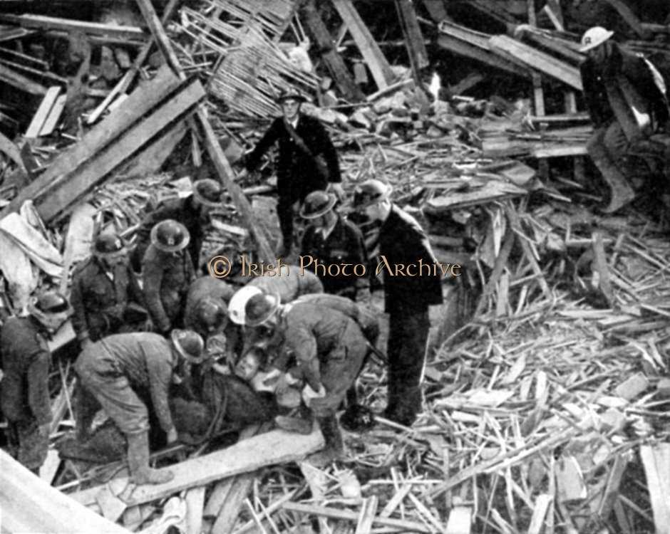 Rescue workers releasing injured person from the debris of a building destroyed by German bombing: 1940.  World War II.
