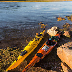 A pair of kayaks next to the Essex River at the Cox Reservation in Essex, Massachusetts.