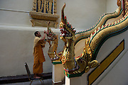 A monk helps add the finishing touches to a repainting of Wat Phra That Doi Suthep,  buddhist pilgrimage site, Chiang Mai, Thailand