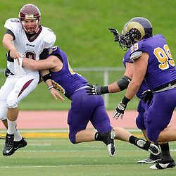 Bloomsburg QB Pat Carey (9) is taken down just as he gets rid of the ball, by West Chester's Mike Labor (43). TK4