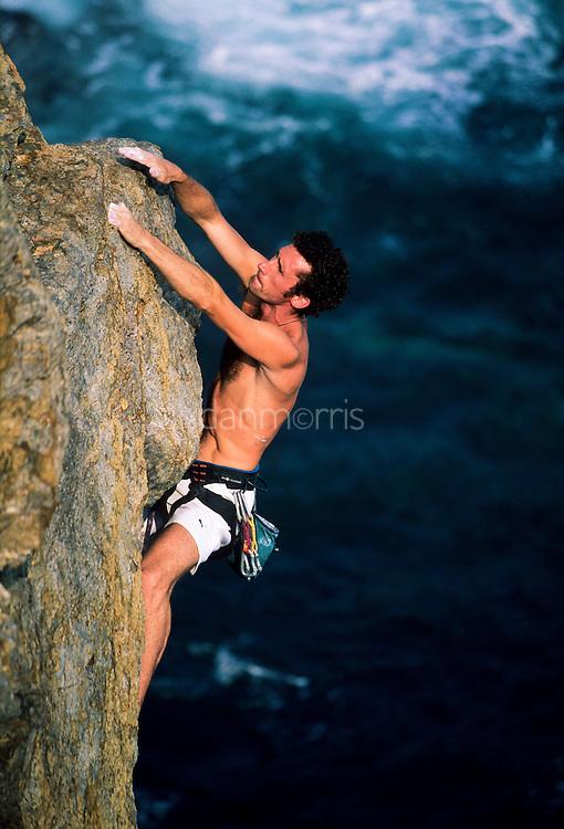 Pete Bailey climbing above crashing waves, Tung Lung Island, Hong Kong