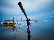29 JULY 2017 - AIRKUNING, BALI, INDONESIA: A fisherman carries the outrigger from his fishing canoe in after returning to shore in Airkuning, a Muslim fishing village on the southwest corner of Bali. Villagers said their regular catch of fish has been diminishing for several years, and that are some mornings that they come back to shore with having caught any fish.    PHOTO BY JACK KURTZ