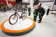 Een vader en zoon vergapen zich aan een racefiets op de beurs BikeMotion in de Jaarbeurs in Utrecht.<br /> <br /> A father watches a racing bike with his son at the trade fair BikeMotion in Utrecht.