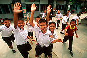 THAILAND, SOUTH, PHUKET ISLAND students waving during recess at a  local Primary School