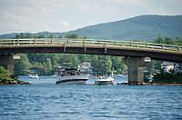 Boaters passing under the Governors Island Bridge on Thursday afternoon.  (Karen Bobotas/for the Laconia Daily Sun)