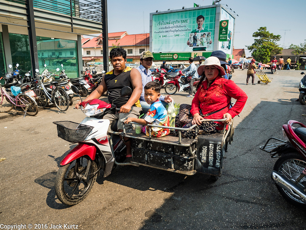 """15 FEBRUARY 2016 - ARANYAPRATHET, SA KAEO, THAILAND: A Cambodian family takes a motorcycle taxi to the crossing point into Cambodia from Aranyaprathet, Thailand. Thais selling bottled water in the border town of Aranyaprathet, opposite Poipet, Cambodia, have reported a surge in sales recently. Cambodian officials told their Thai counterparts that because of the 2016 drought, which is affecting Thailand and Cambodia, there have been spot shortages of drinking water near the Thai-Cambodian and that """"water shortages in Cambodia had prompted people to hoard drinking water from Thailand.""""     PHOTO BY JACK KURTZ"""