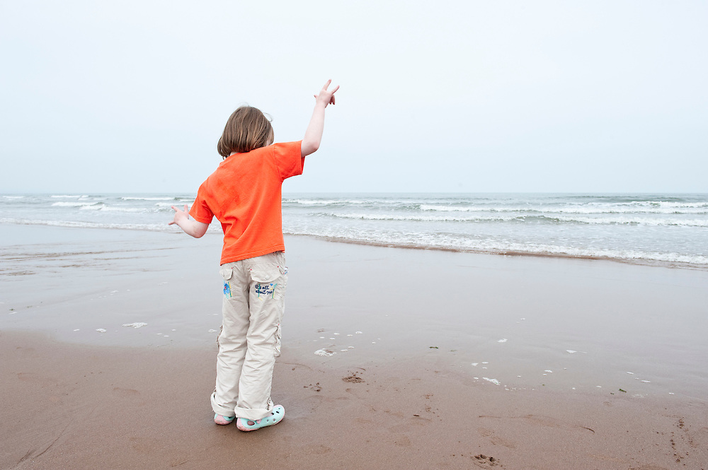 Young girl dancing on a beach, Scotland