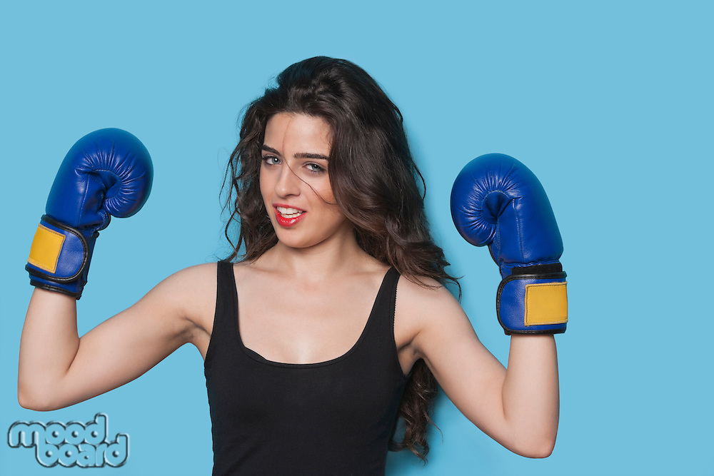 Portrait of a beautiful young female boxer raising arms in victory against blue background
