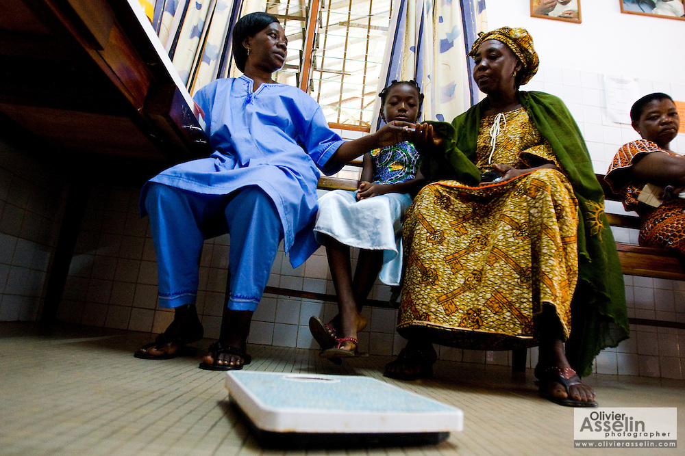 Nurse Cécile Aka Ahoua gives painkillers for seven-year-old daughter Aishata Konante who waits with her mother Ahoua Konante at the NDA health center in Dimbokro, Cote d'Ivoire on Friday June 19, 2009. Aishata suffers from fever, cough and muscle pains.