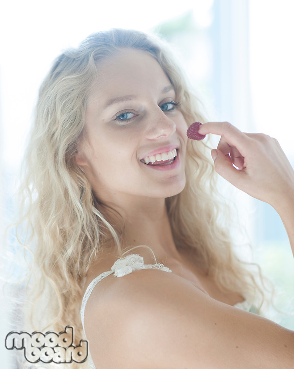 Portrait of woman with raspberry on fingertips