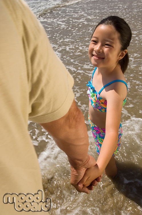 Girl Holding Father's Hand on Beach