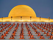 "11 FEBRUARY 2016 - KHLONG LUANG, PATHUM THANI, THAILAND:  Buddhist monks pray in their seats on the pagoda during the Makha Bucha Day service at Wat Phra Dhammakaya.  Makha Bucha Day is a public holiday in Cambodia, Laos, Myanmar and Thailand. Many people go to the temple to perform merit-making activities on Makha Bucha Day, which marks four important events in Buddhism: 1,250 disciples came to see the Buddha without being summoned, all of them were Arhantas, or Enlightened Ones, and all were ordained by the Buddha himself. The Buddha gave those Arhantas the principles of Buddhism. In Thailand, this teaching has been dubbed the ""Heart of Buddhism."" Wat Phra Dhammakaya is the center of the Dhammakaya Movement, a Buddhist sect founded in the 1970s and led by Phra Dhammachayo. Makha Bucha Day is one of the most important holy days on the Thai Buddhist calender.     PHOTO BY JACK KURTZ"