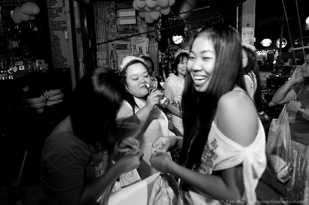 """Women from Empower distribute Empower-branded condoms on Valentine's Day to sex workers in Chiang Mai, Thailand. Run by sex workers, Empower has a drop-in center offering computer and informal English training, health education, counseling and other support to sex workers. Founded in 1985 the organization has five centers from Phuket to Mai Sai and advocates for recognition, equality, and basic human rights for sex workers in Thai society where sex work is common, visible, and yet illegal..>>.Empower Chiang Mai opened the """"Can-Do"""" bar which offers fair working conditions to sex workers by complying with all Thai Labor Laws and the recommended occupational health and safety standards..>>.Empower, which works with women over 18 years-old and is a vocal opponent of human trafficking, sexual or labor exploitation of any person,  is also campaigning to change the methods of anti-human trafficking groups. Empower states """"the focus on trafficking in persons has meant many groups with little or no experience on the issues of migration, labor, sex work or women's rights have been created to take advantage of the large sums of money available to support anti-trafficking activities."""".>>.Recommendations by sex workers, many who were Burmese, some who had been trafficked, and all who acknowledged enlisting an agent to migrate illegally into Thailand, stated among other things that """"The primary goal of prosecuting traffickers must be altered to a primary goal of assisting trafficked women and children...if trafficked women and children...are continually rescued and assisted, the use of trafficked women and children will become unprofitable...we are willing to work our illegal status leaves us with no recourse against exploitation by agents or employers...Anti-trafficking groups must work toward improving the human rights situation...Anti-trafficking dialogue and groups have yet to consider us as anti-trafficking workers and human rights defenders...The latest stance from the USA"""