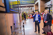 01 OCTOBER 2012 - BANGKOK, THAILAND: Departing passengers look at the flight status board on the first day of international flights from Don Mueang International Airport in Bangkok Monday. Don Mueang International Airport is the smaller of two international airports serving Bangkok, Thailand. Suvarnabhumi Airport, opened in 2006 is the main one. Don Mueang was officially opened as a Royal Thai Air Force base on 27 March 1914 and commercial flights began in 1924. Don Mueang Airport closed in 2006 following the opening of Bangkok's new Suvarnabhumi Airport, and reopened as a domestic terminal for low cost airlines after renovation on 24 March 2007. Closed during the flooding in 2011, Don Mueang was again renovated and reopened in 2012 as the airport for low cost airlines serving both domestic and international passengers. On Monday, Air Asia, Asia's leading low cost airline, transferred all of their flight operations to Don Mueang and the airport was officially reopened. Suvarnabhumi International Airport is already over capacity and Don Mueang's importance as a hub is expected to grow.    PHOTO BY JACK KURTZ