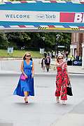 "Two ladies under the ""Welcome To York"" bridge at the York Dante Meeting at York Racecourse, York, United Kingdom on 17 May 2018. Picture by Mick Atkins."