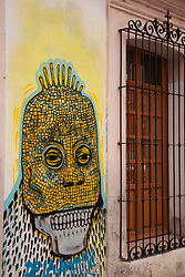 North America, Mexico, Oaxaca Province, Oaxaca, skull mural and wrought-iron window grill, Day of the Dead (Dias de los Muertos) celebration