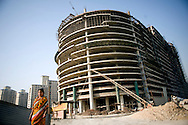 A woman makes her way past a construction site in New Delhi, India February 23, 2009. Asia's third-largest economy will probably expand 7.1 percent in the year ending March 31 according to a statement by the country's statistics office in New Delhi.