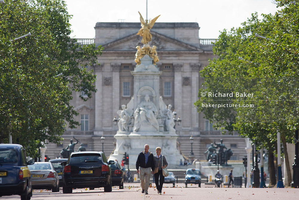 A couple walk down the centre of the Mall away from the Victoria Memorial and the Queen's Buckingham Palace in London