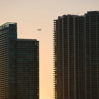 Passenger aircraft flying over skyscrapers at sunset, MIami, Florida, USA