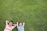 Portrait of two boys (6-11) lying on grass hands behind head