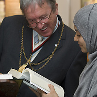 Young womanwearing hijab, showing a Quran to a westerner man<br />