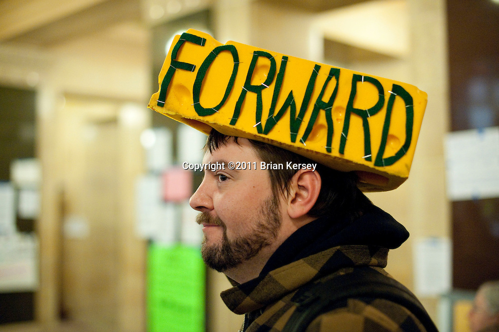 Kevin Kopplin wears a cheesehead adorned with the Wisconsin state motto at the state Capitol in Madison, Wisconsin on February 24, 2011. Protests over budget legislation continued for the 11th day as a bill slashing benefits and revoking collective bargaining rights from state workers nears passage.     (Photo by Brian Kersey)