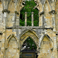 William Etty Tomb near St Mary&rsquo;s Abbey in York, England <br /> Walking among the ruins of St Mary&rsquo;s Abbey in the Museum Gardens is a visual treat. It is easy to see how magnificent this church must have been when it was finished in 1295. What is easy to overlook is behind this arched gate. There in the graveyard of the adjoining St Olave&rsquo;s Church is the tomb of William Etty. He was a local painter (1787 &ndash; 1849) who became famous with his depictions of nudes. The largest collection of his work is exhibited at the York Art Gallery.