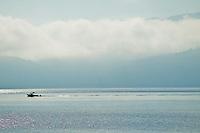 A boat cruises across Lake Coeur d'Alene as the early morning fog settles across the hillsides lining the shoreline.