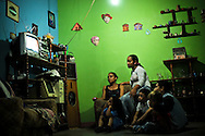 "Isaura Romero, 38, (left) and Yelitza Lopez, 19, (right) watch television in Ms. Romero's home with her children in the ""Tower of David."""
