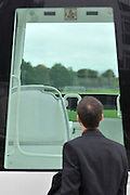 HEDNON LONDON. Father Stephen Wang, who is due to meet with the Pope on Sunday inspects the Pontiff's Popemobil. One of the Popemobiles to be used during the Popes visit to Britain later this week is unveiled to the media at Hendon Police Academy, London. Two of the celebrated vehicles, complete with bullet-proof glass enclosures, were shipped into Britain ahead of the Pontiff's planned visit in September. The vehicles, with the registration plate SCV 1, or SCV, standing for Stato della Citta del Vaticano, the Italian name for Vatican City, are driven at low speed to allow crowds a chance to view the Pope. 14 September 2010. STEPHEN SIMPSON