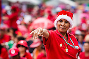 19 MAY 2013 - BANGKOK, THAILAND:     A Red Shirt wearing a Santa Claus hat cheers during a Red Shirt rally in Ratchaprasong Intersection honoring Red Shirts killed by the Thai army in 2010. More than 85 people, most of them civilians, were killed during the Thai army crackdown against the Red Shirt protesters in April and May 2010. The Red Shirts were protesting against the government of Abhisit Vejjajiva, a member of the opposition who became Prime Minister after Thai courts ruled the Red Shirt supported government was unconstitutional. The protests rocked Bangkok from March 2010 until May 19, 2010 when Thai troops swept through the protest areas arresting hundreds.   PHOTO BY JACK KURTZ
